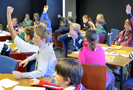 Kids enthusiastically shoot their hands up during a design workshop in the Bigger Things project
