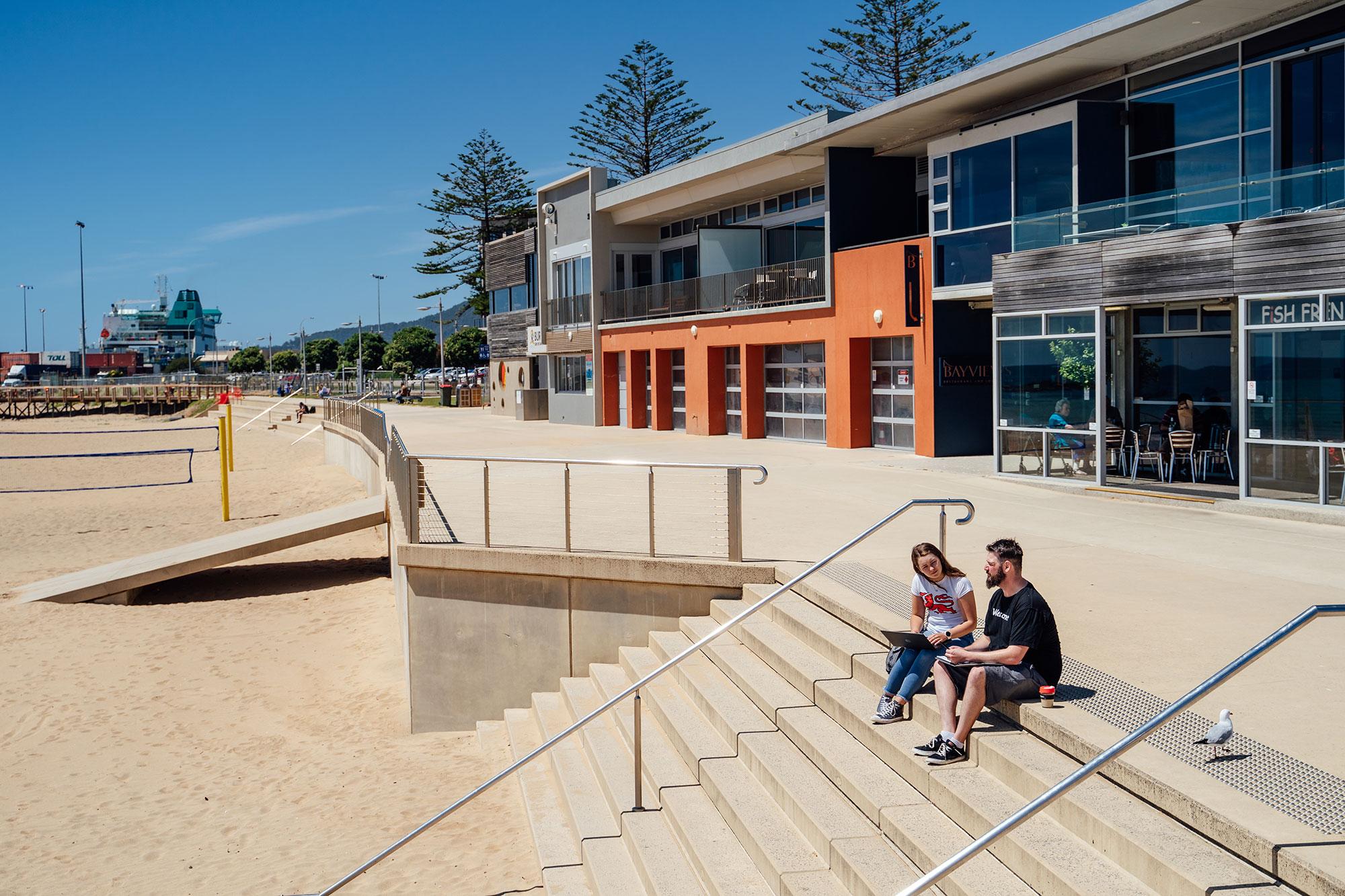 Students sitting on steps at Burnie campus waterfront boardwalk
