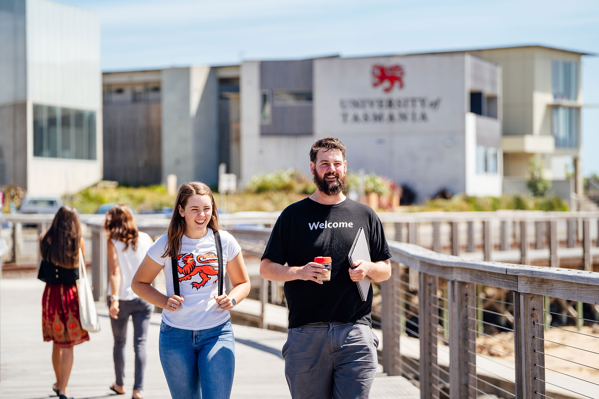 Students walking along Burnie's boardwalk, with campus in the background.