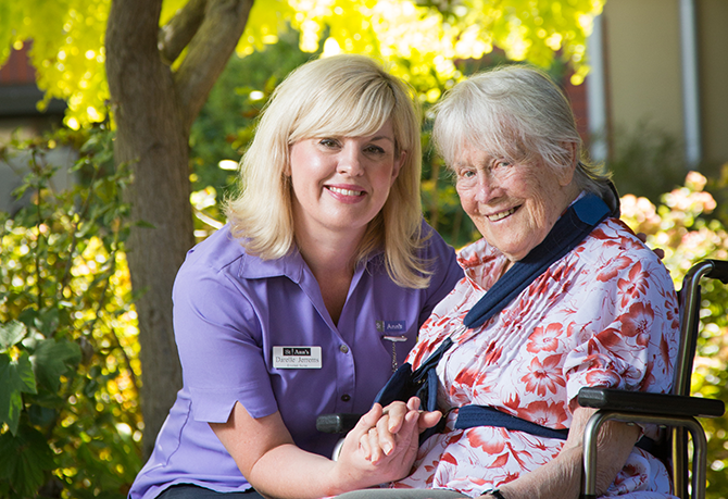 A nurse and an ederly woman sitting outdoors