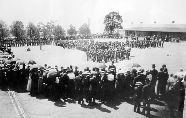 A crowd watches soldiers on parade in 1899, during the South African War